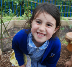 girl in school uniforms smile at camera as part of school growing project in Manchester